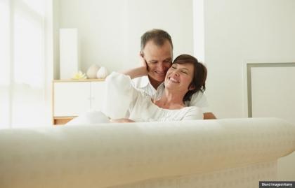 Pareja acariciándose en un sofa - Una guía a las relaciones sexuales después del cáncer de mama.