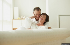 Couple cuddling together on sofa. A guide to sex after breast cancer. (Blend Images/Alamy)
