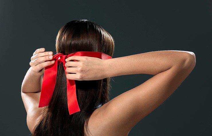 Woman tying ribbon over eyes. The joy of blindfolds.