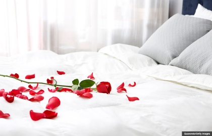 Bed with rose petals. Six sensual strategies. (Quavondo/Getty Images)
