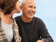 Mujer susurrando en el oído de un hombre - Amigos con derechos después de los 50
