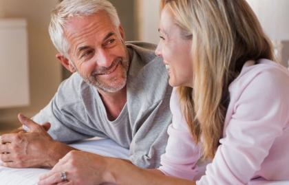 Pareja joven hablando juntos en la cama, se puede tener relaciones sexuales después del cáncer de próstata