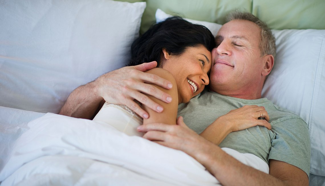 Couple Hug And Laugh In Bed Together, AARP Home And Family, Relationships, Sex And Intimacy, Which Comes First? Desire Or Sex?