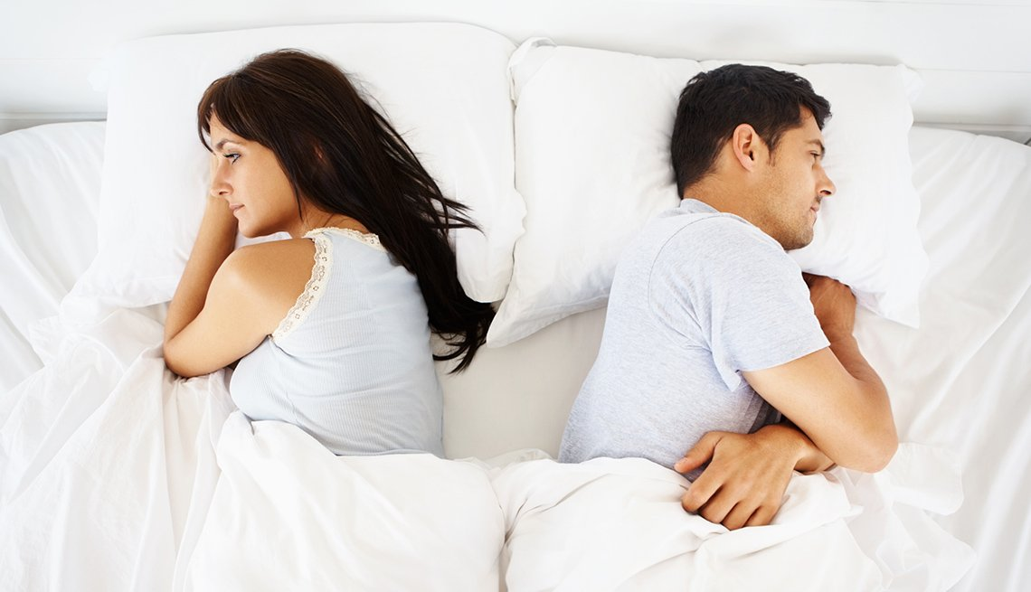 Angry Couple Facing Away From Each Other In Bed, AARP Home And Family, Sex And Intimacy, Relationships, Destructive Relationship Myths