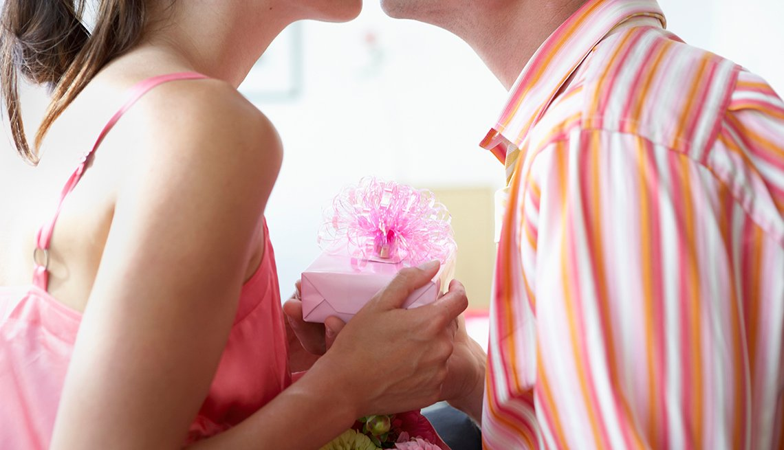 Couple Kiss Holding Pink Present, Woman in Pink Top, Man in Striped Shirt,  8 Ways to Celebrate Your Husband (or Wife). Tonight!