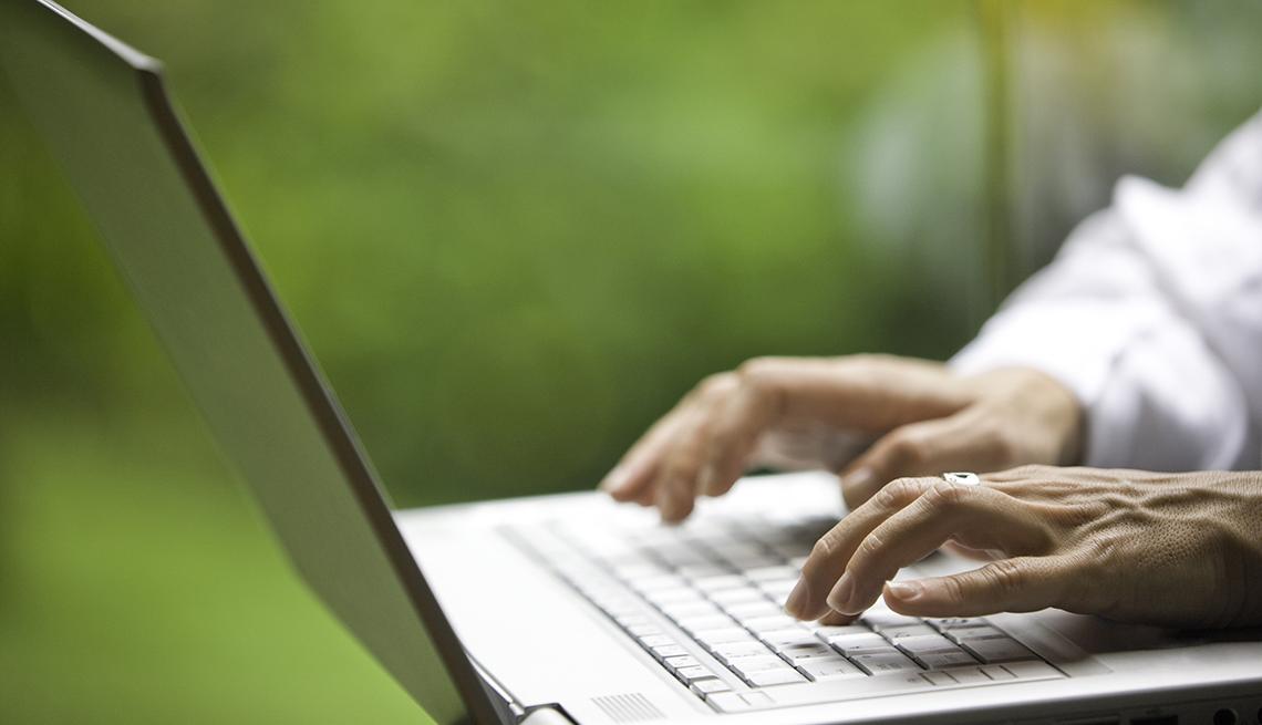 Manos de persona mayor sobre el teclado de computador portátil