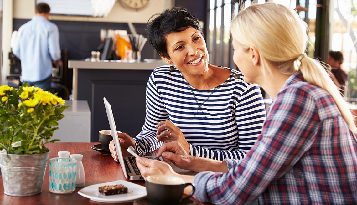 Mujeres conversando en un cafe con computador portátil frente a ellas