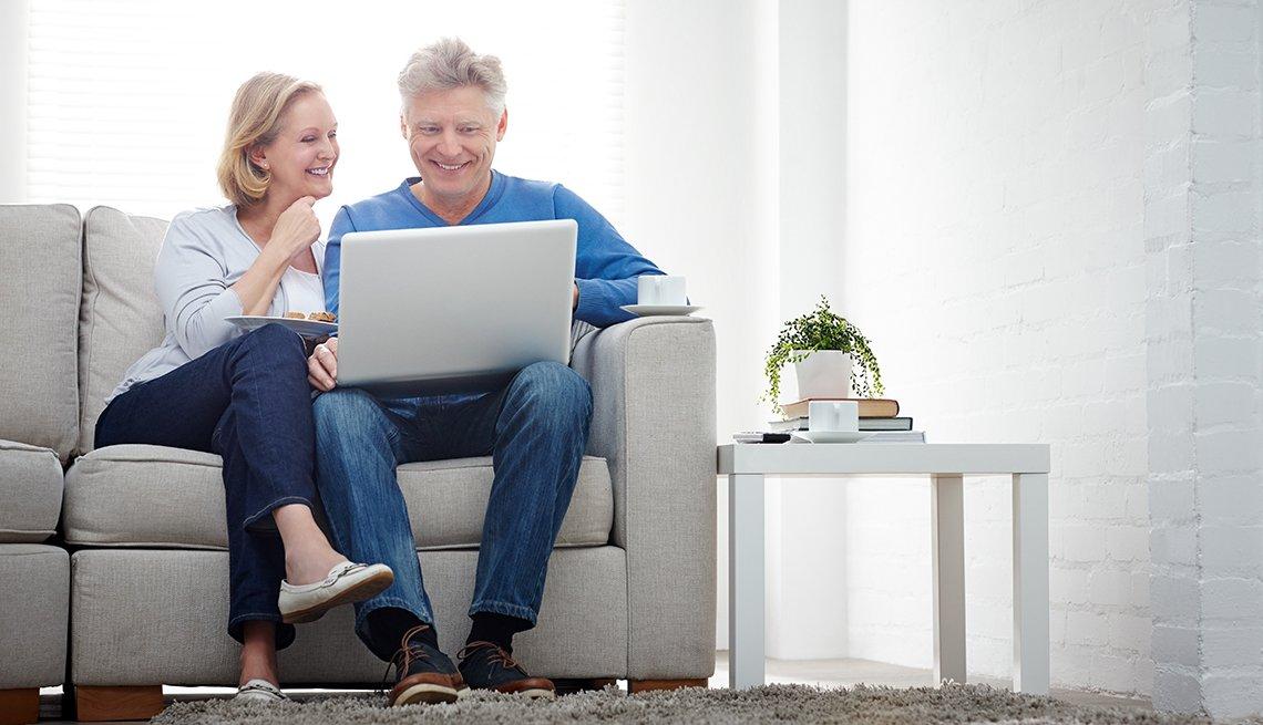 Pareja mayor sentada en sofa, sonriendo enfrente se un computador portátil
