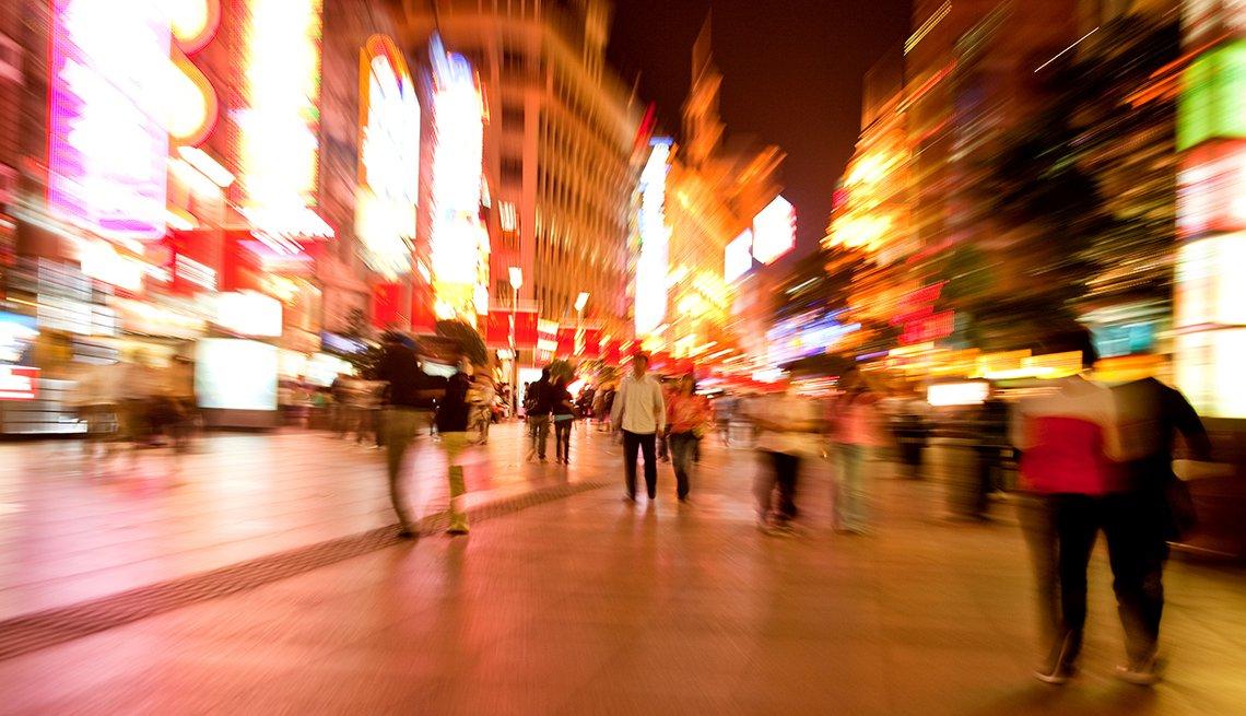 Personas caminando en la calle al anochecer