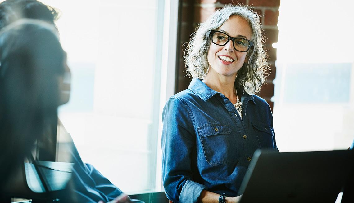 Mujer mayor con gafas trabajando en un computador y sonriendo con sus colegas en una oficina