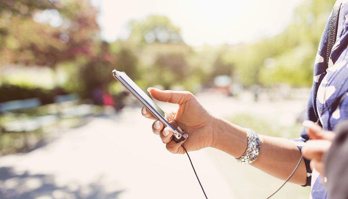 Mujer sostiene en la mano un teléfono inteligente