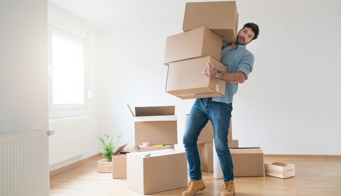 Un hombre sostiene con dificultad tres cajas de cartón.