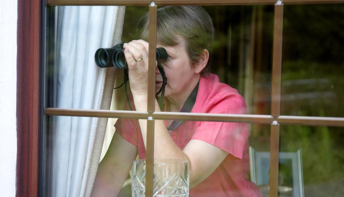 Una mujer observa por la ventana con unos binoculares.