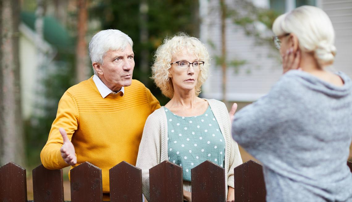 Una pareja habla a través de la cerca de su casa con su vecina.
