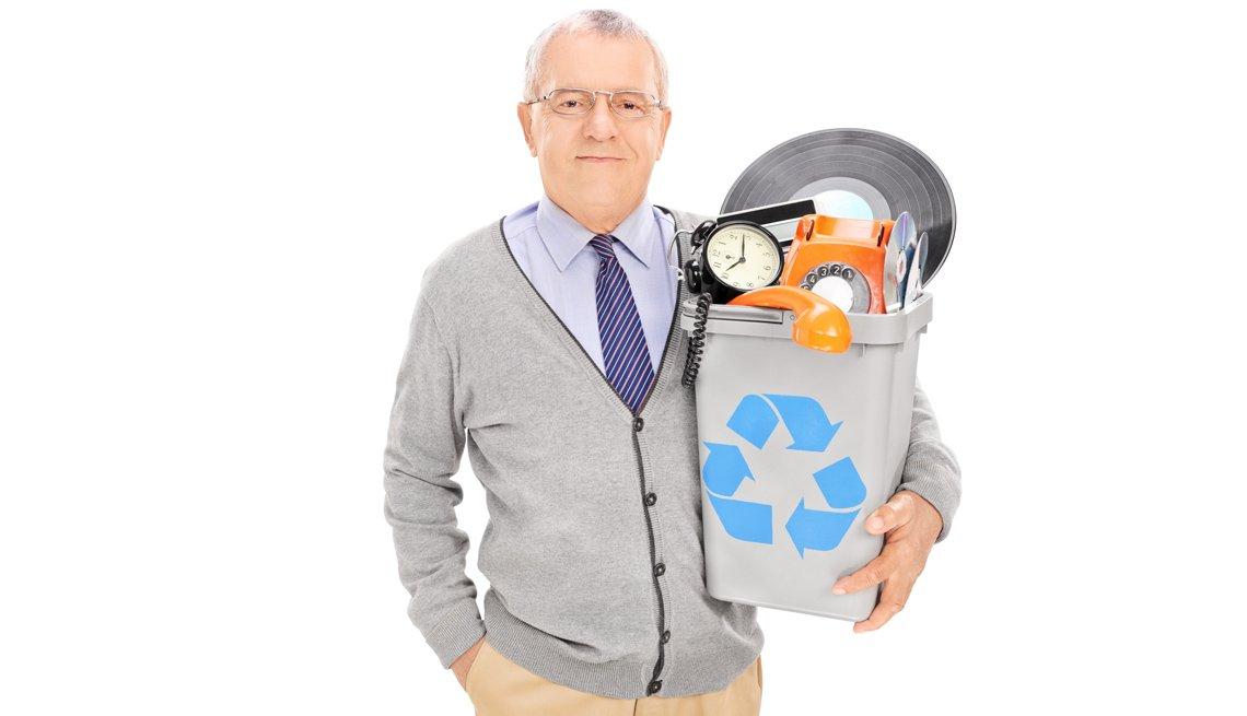 Un hombre mayor sostiene una papelera de reciclaje llena de cosas viejas
