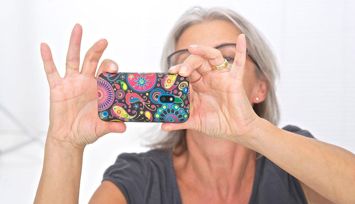 Mujer mayor tomandose una foto con su teléfono móvil