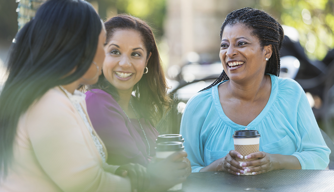 Group of three multi-ethnic women sitting around an outdoor table on a patio drinking coffee and conversing.  The woman in purple is mixed race African-American. The focus is on her African-American friend wearing blue.