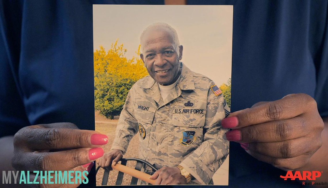Woman holds a photo of an older man in an armed forces uniform.