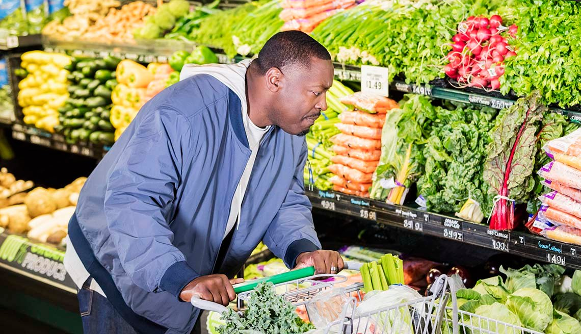 A mature African-American man in his 40s shopping in the produce section of a supermarket, pushing a shopping cart. He has a serious expression on his face, perhaps not finding the vegetable he is looking for.