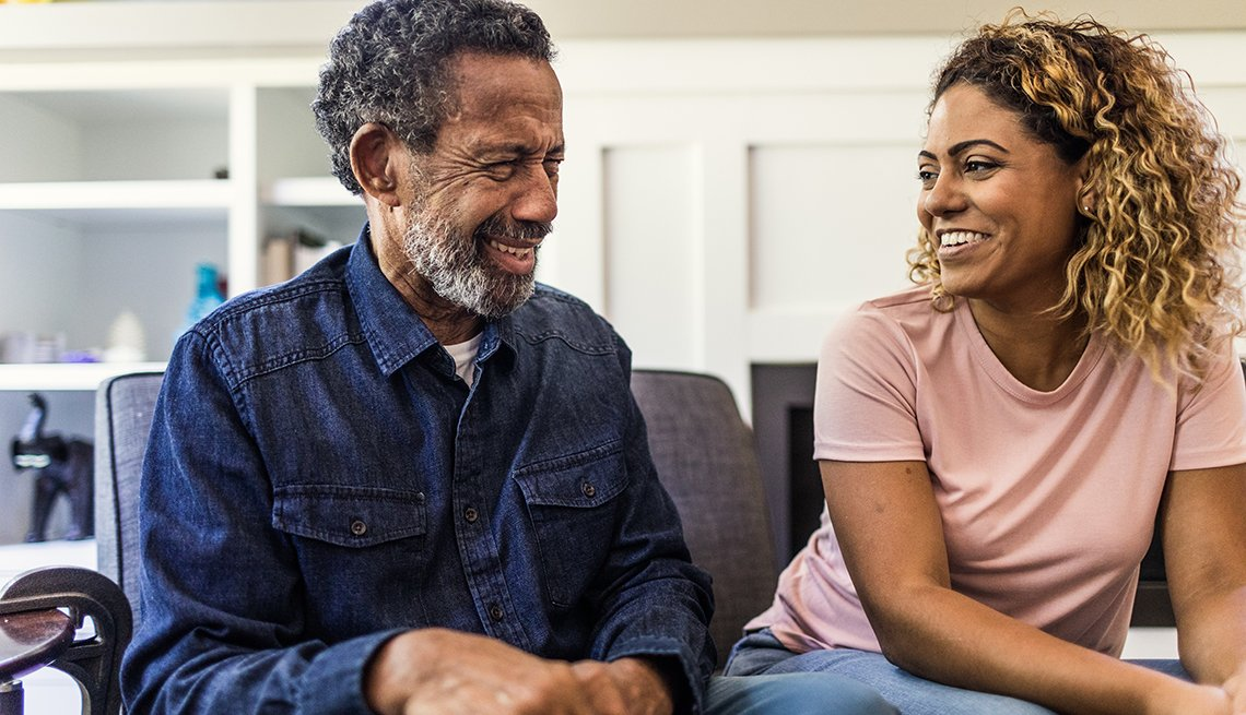 Older man with his daughter in living room smiling