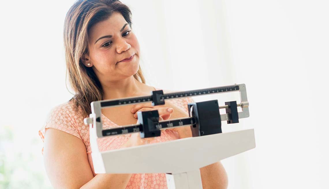 Women weighs herself on a scale
