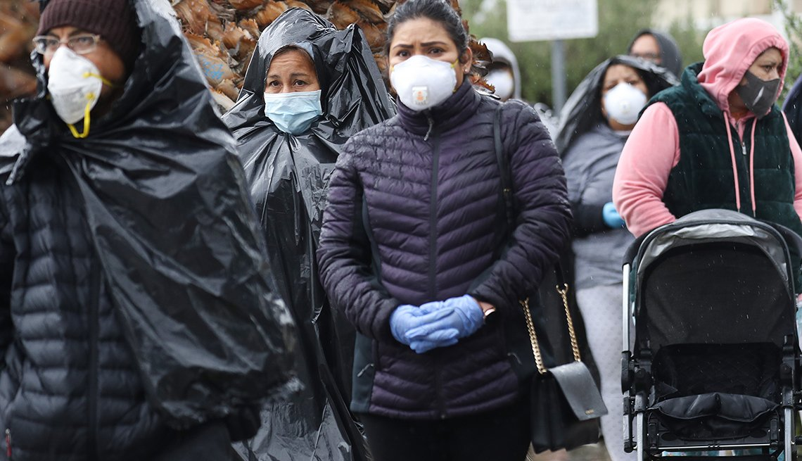 Juana Gomez (2nd L), from North Hollywood, wears a face mask, while using a trash bag to protect against the rain, as she waits in line to receive food at a Food Bank distribution for those in need as the coronavirus pandemic continues on April 9, 2020