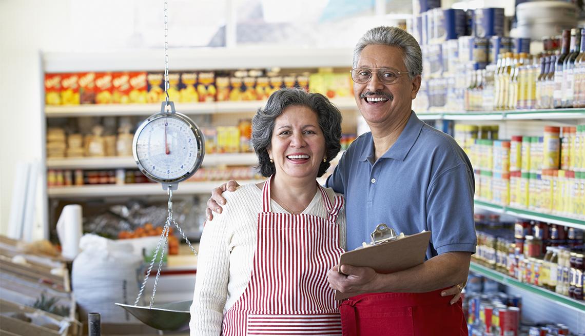 Una pareja de adultos mayores sonríe en su tienda de comestibles