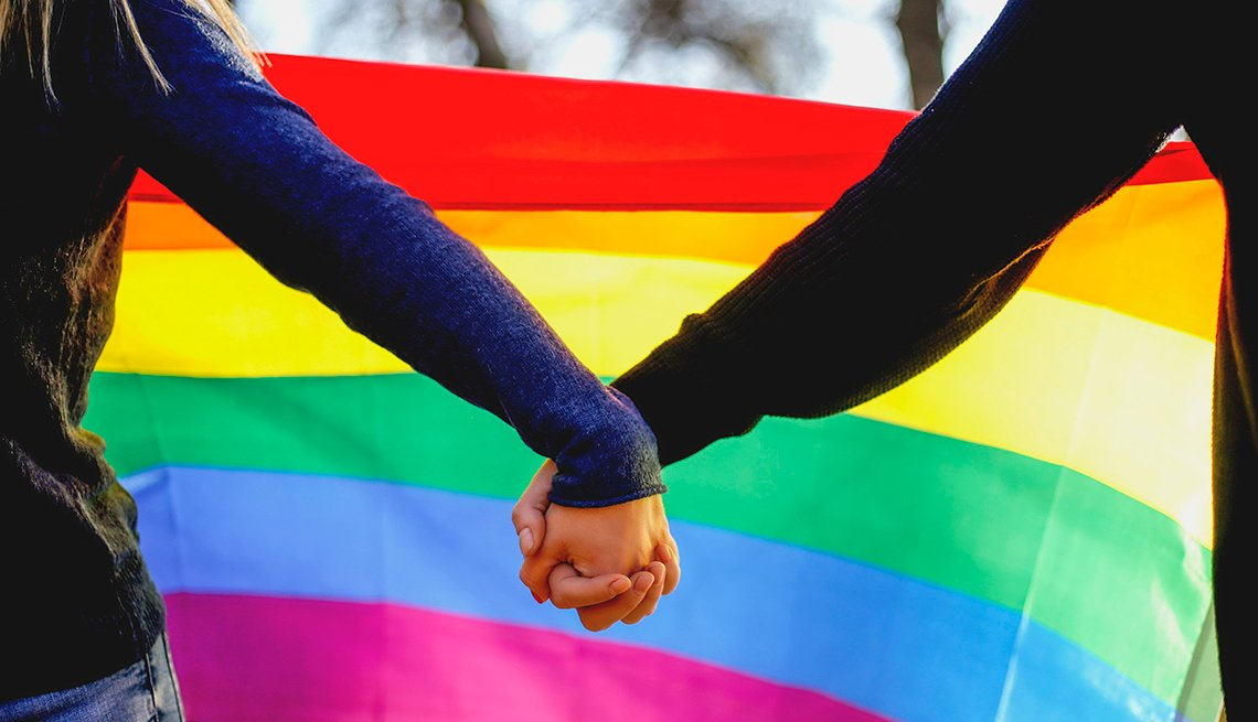 Two girls holding hands and a rainbow flag in support of the LGBT community