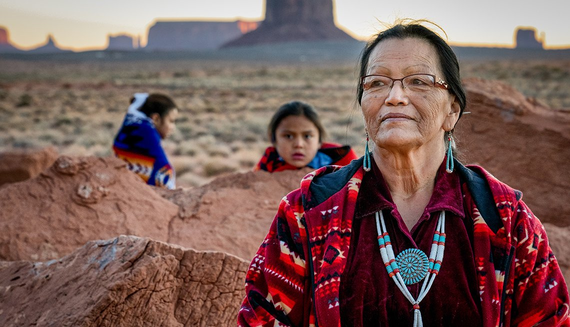 Portrait of a traditional Navajo grandmother with her grandson and granddaughter in front of the famous rock formations of the Monument Valley Tribal Park in Northern Arizona