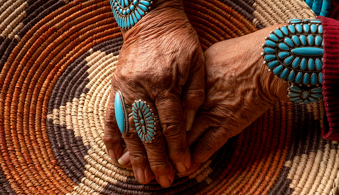 Senior Navajo woman posing with traditional turquoise jewelry inside an authentic hogan