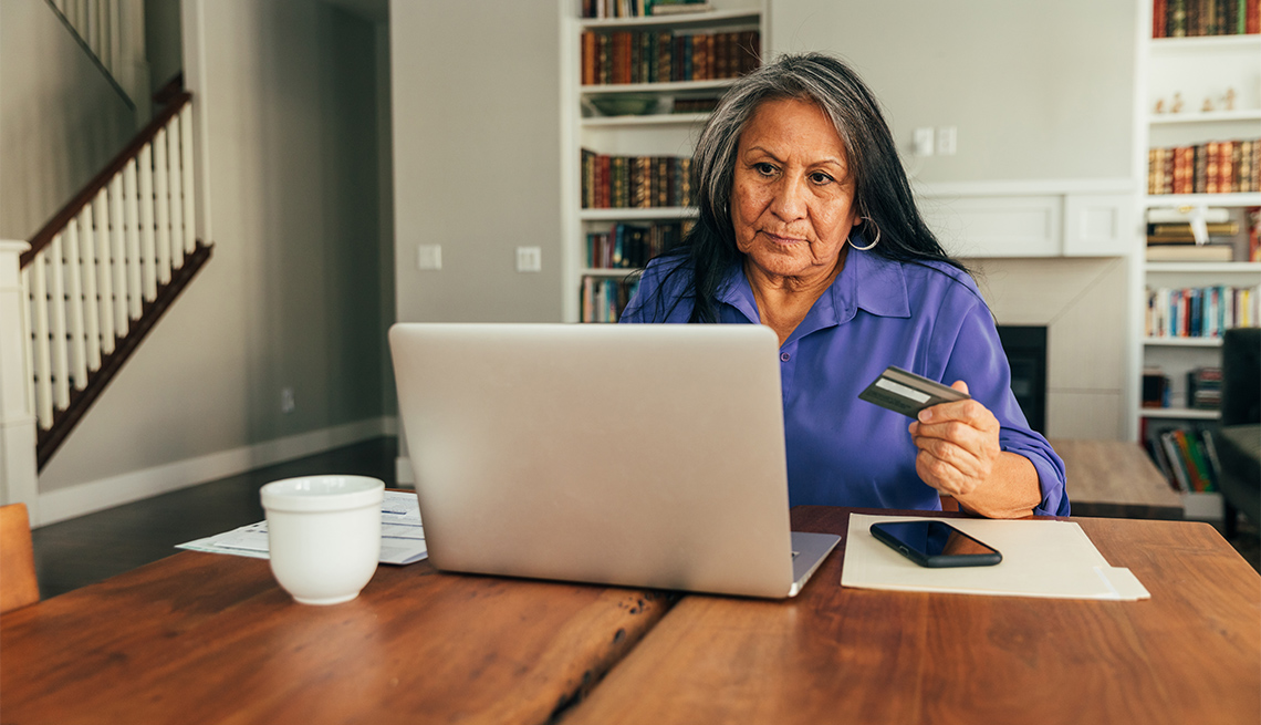 A adult woman sits at the dining table paying bills