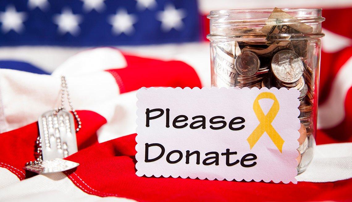 Jarra con monedas sobre una bandera de Estados Unidos y el letrero por favor done