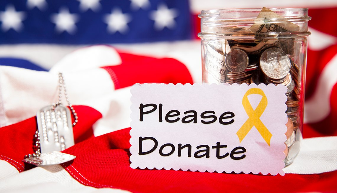 Please donate sign on an American flag with dog tags and a jar of money.