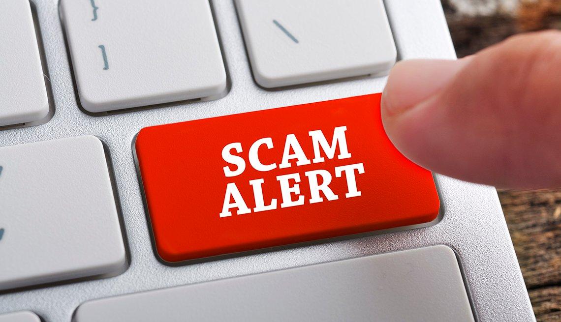 Un dedo que va a tocar una tecla que dice, alerta de fraude, en inglés.