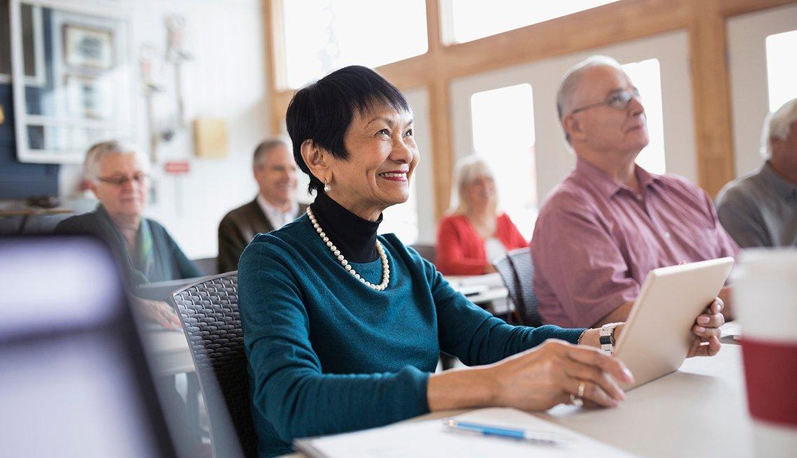 Mujer mayor sonríe mientras sostiene una tableta electrónica.