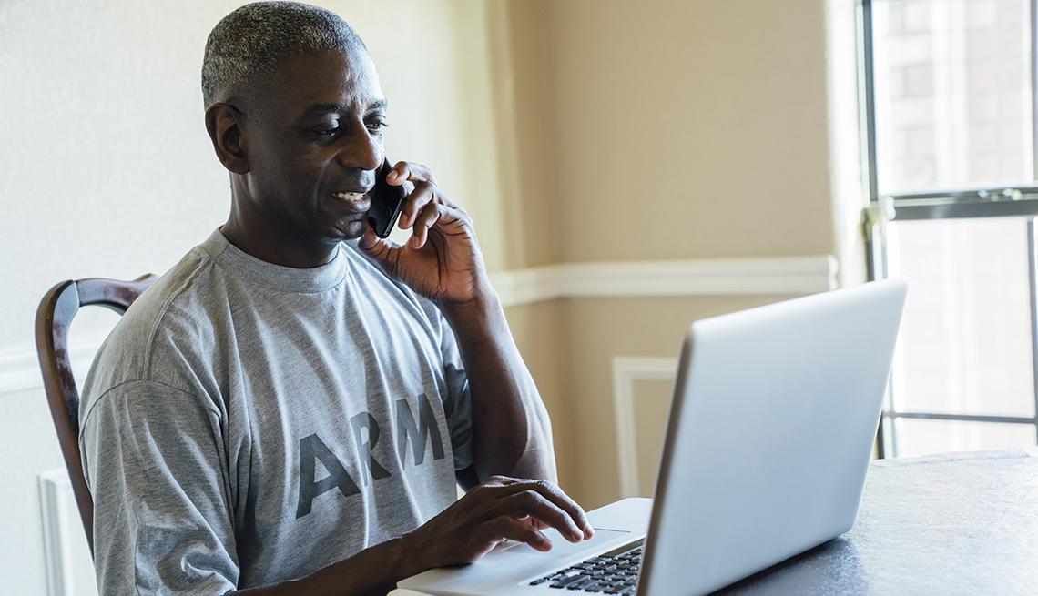 Hombre usando el computador mientras habla por teléfono.