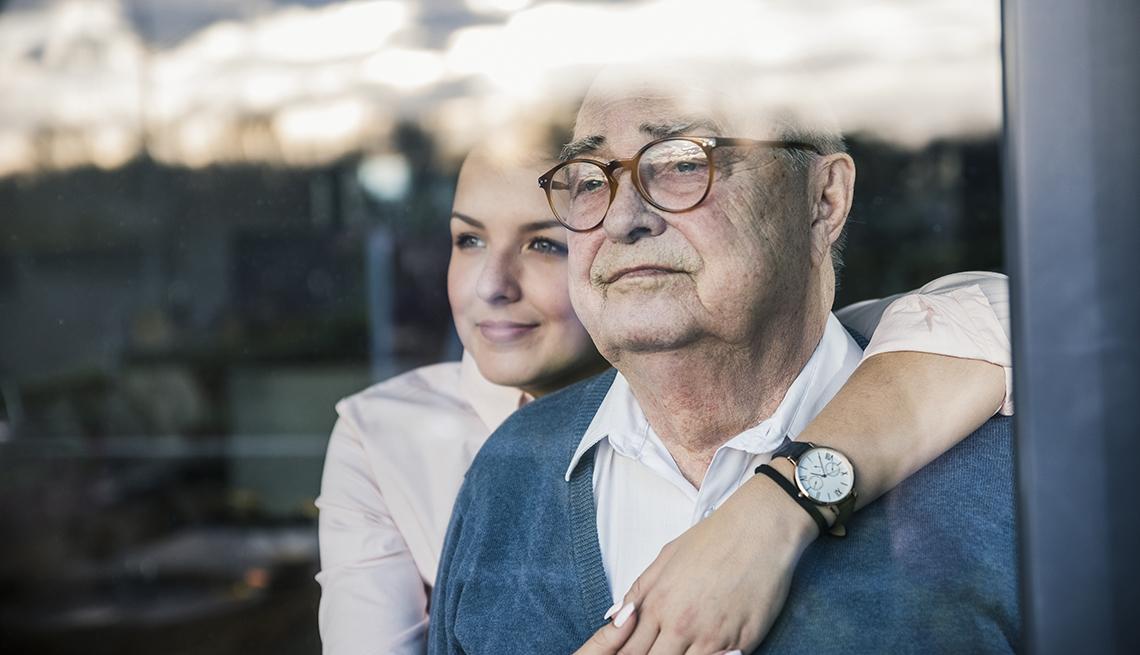 Una mujer joven y un hombre mayor observan a través de una ventana.