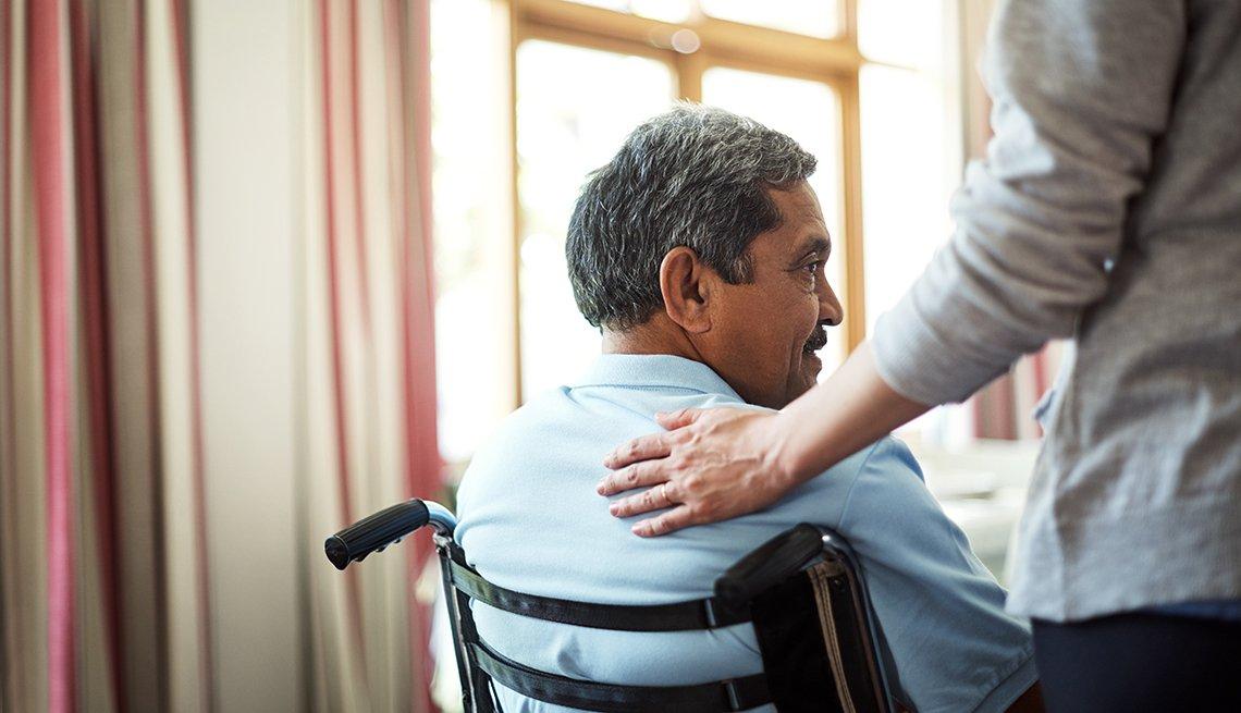 Una joven enfermera cuida a un hombre mayor en una casa de retiro.