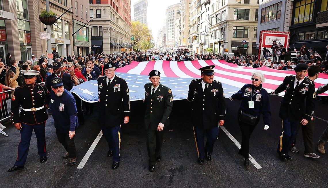Grupo de veteranos carga la bandera de Estados Unidos mientras camina en la calle.