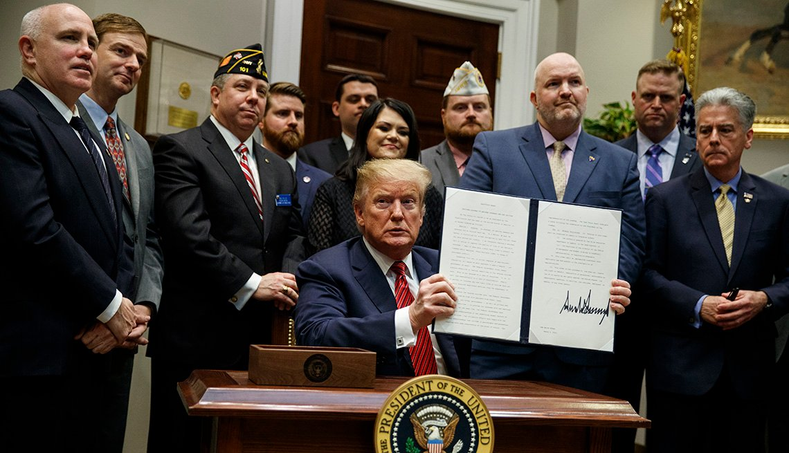 President Donald Trump shows off an executive order on a