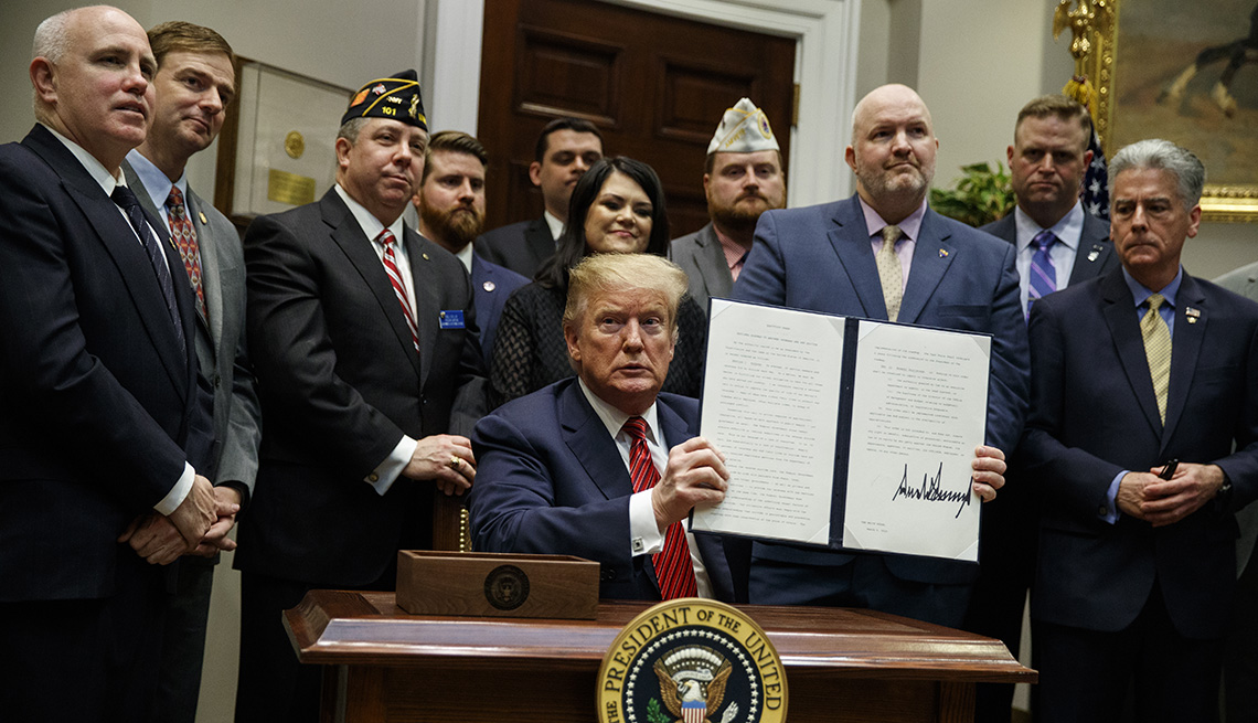 "President Donald Trump shows off an executive order on a ""National Roadmap to Empower Veterans and End Veteran Suicide,"" in the Roosevelt Room of the White House, Tuesday, March 5, 2019, in Washington"