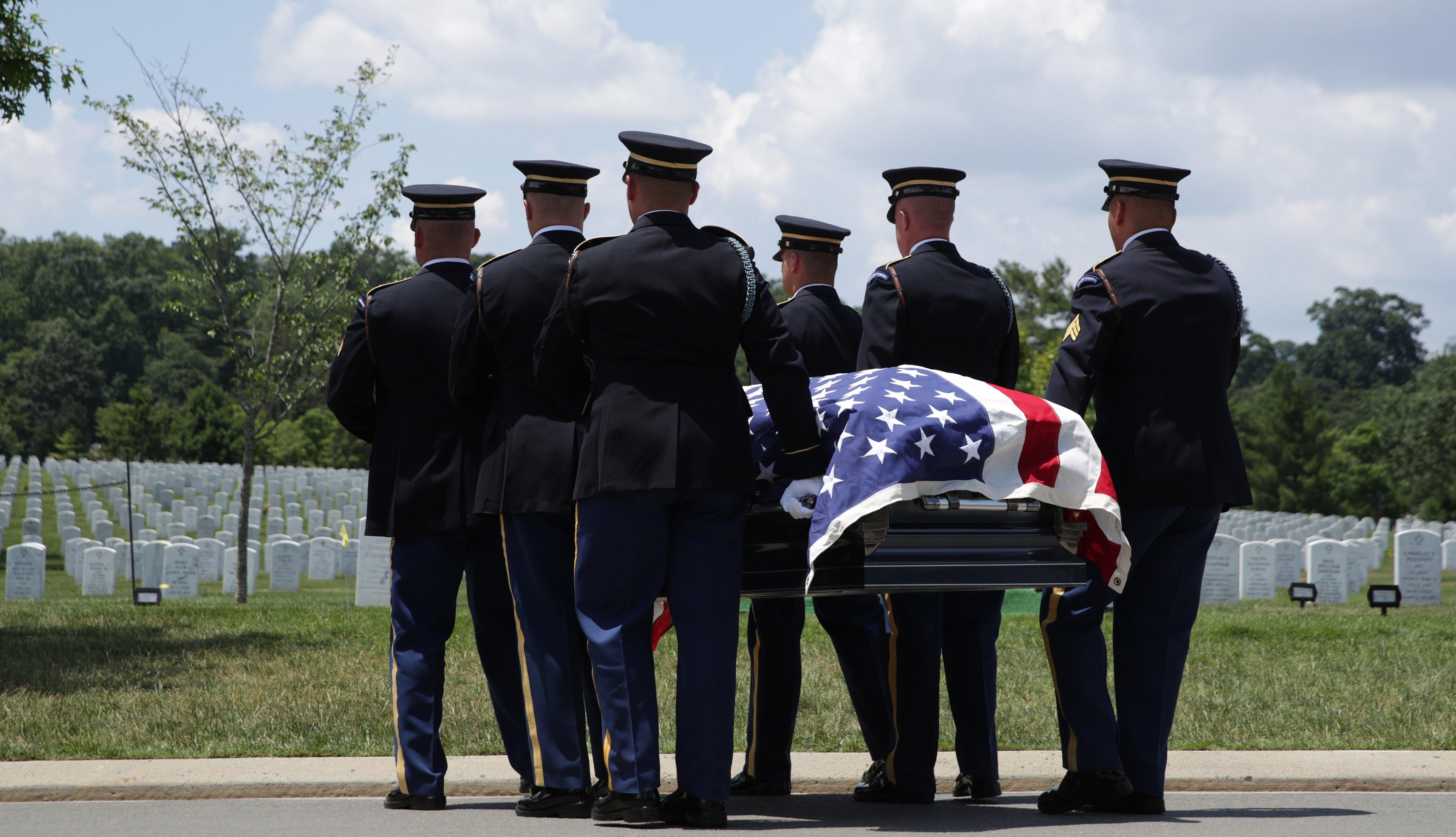 Hombres en uniforme llevan un ataúd envuelto en la bandera estadounidense en un cementerio