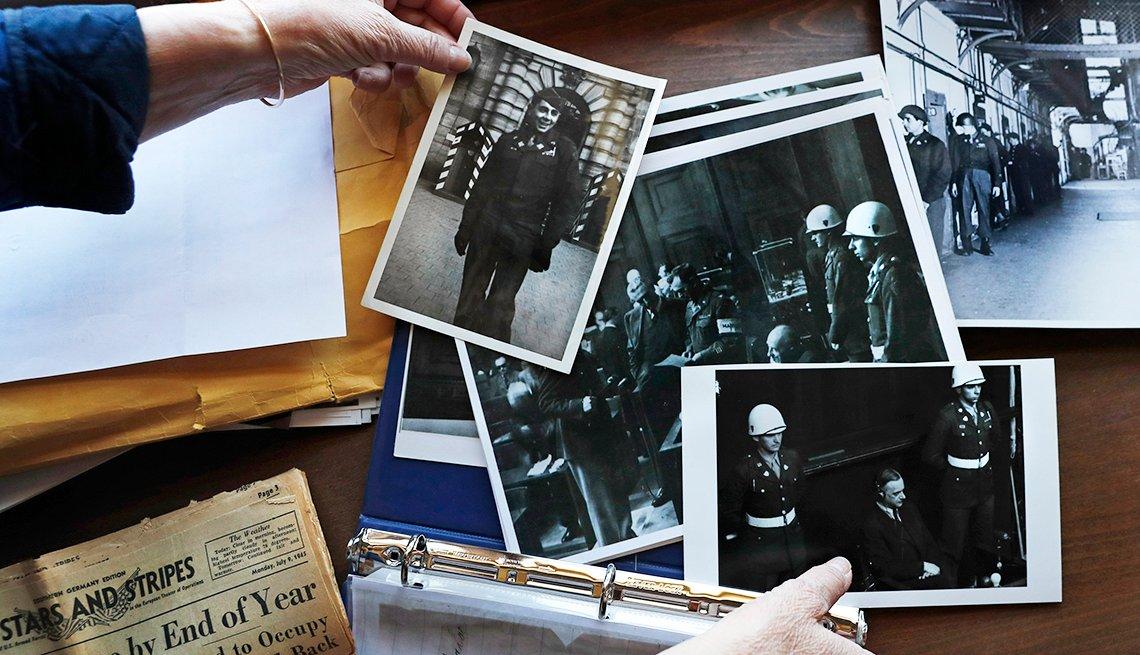 Manos arreglan una serie de fotografías antiguas con un hombre en uniforme.