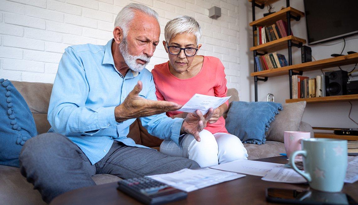Un hombre y una mujer están sentados en el sofá mirando facturas