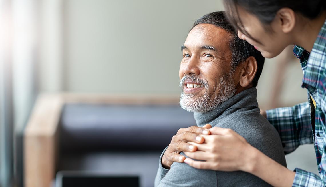 Mujer pone su mano en el hombro de un hombre que sonríe