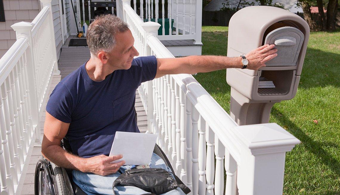 Un hombre en silla de ruedas recoge el correo de su buzón