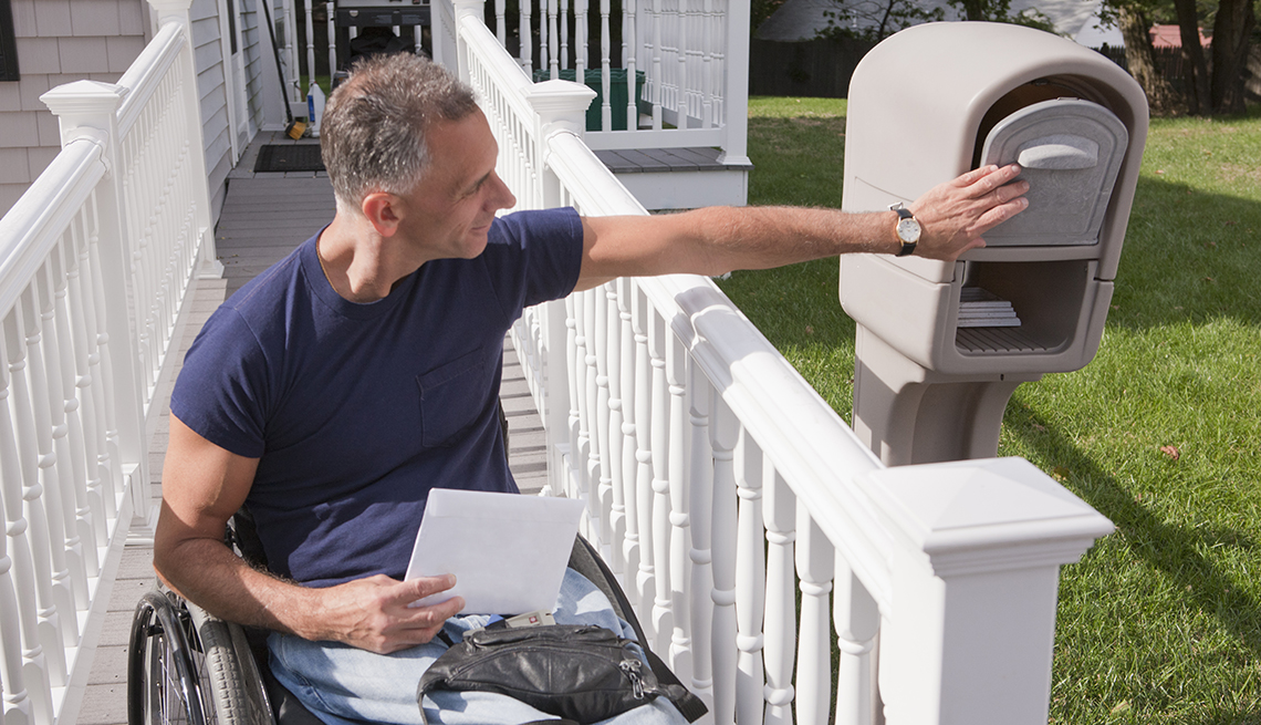 A man in a wheelchair is getting mail out of his mailbox