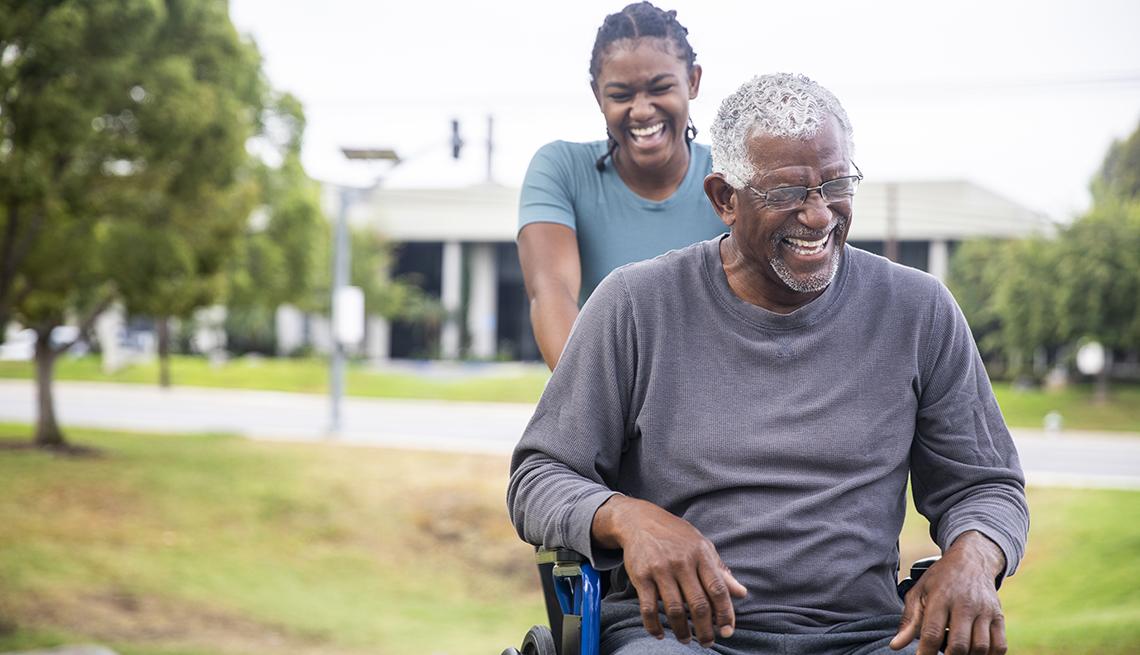 Una mujer empuja a un hombre que va en silla de ruedas