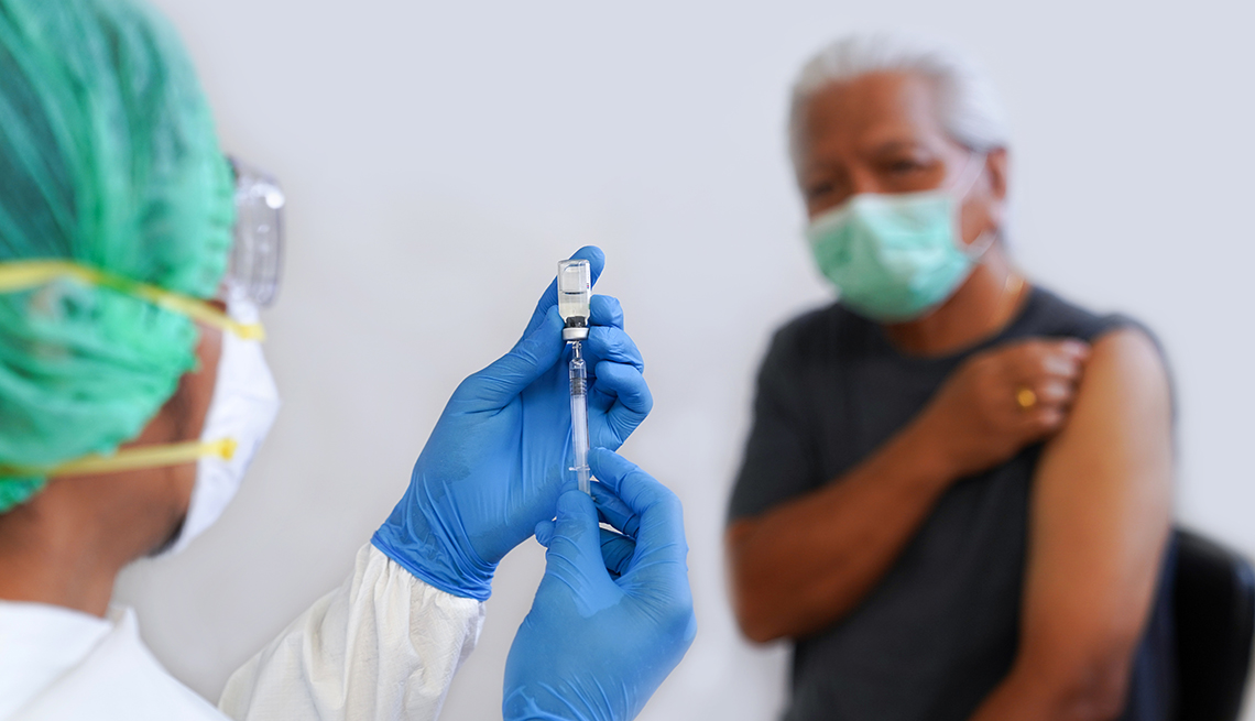 Un médico está a punto de aplicar una inyección a un paciente