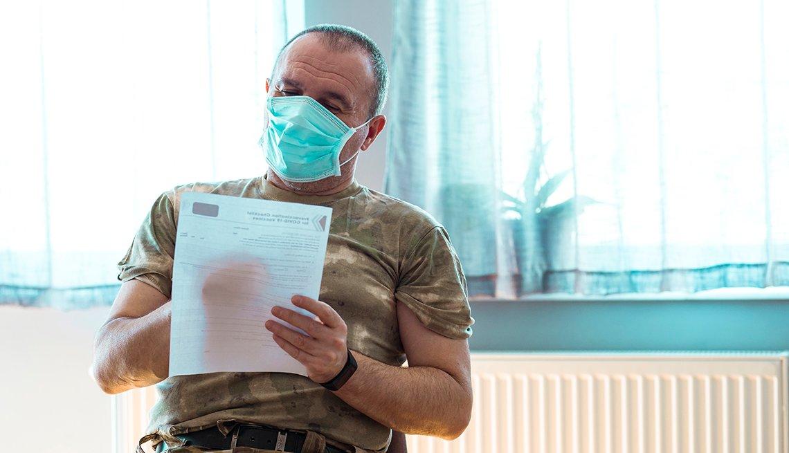 Un veterano militar con una máscara quirúrgica llena un formulario de vacunación contra la COVID-19